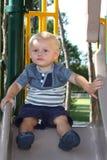 Criança que joga em uma corrediça Fotografia de Stock Royalty Free
