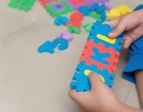 Criança que joga enigmas de serra de vaivém do alfabeto Foto de Stock Royalty Free