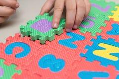 Criança que joga enigmas de serra de vaivém do alfabeto Imagens de Stock