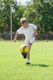 Criança que joga a esfera de futebol foto de stock royalty free
