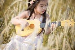 Criança que joga a guitarra ao prado exterior na natureza fotos de stock