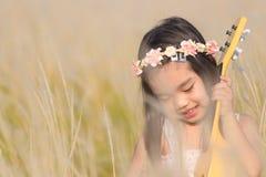 Criança que joga a guitarra ao prado na natureza no dia ensolarado fotografia de stock royalty free