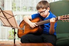 Criança que joga a guitarra em casa imagens de stock