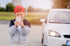 Criança que joga jogos móveis no smartphone na rua Imagem de Stock Royalty Free