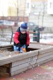 Criança que joga na caixa de areia Fotografia de Stock Royalty Free