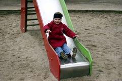 Criança que joga na corrediça Imagens de Stock