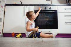 Criança que joga na cozinha com um fogão de gás Fotos de Stock