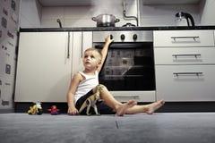 Criança que joga na cozinha com um fogão de gás Imagens de Stock Royalty Free