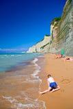 Criança que joga na praia no console de Corfu foto de stock royalty free