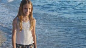 Criança que joga na praia no por do sol, criança feliz que anda na menina das ondas do mar no beira-mar filme