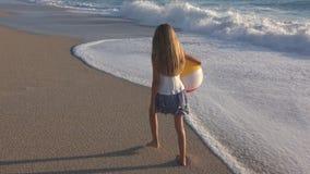 Criança que joga na praia no por do sol, criança feliz que anda na menina das ondas do mar no beira-mar vídeos de arquivo