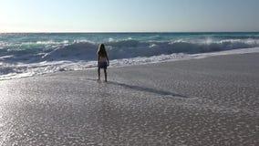 Criança que joga na praia, ondas de observação do mar, menina que corre no litoral no verão video estoque