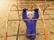 Criança que joga no campo de jogos no dia de mola fresco fotos de stock