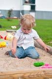Criança que joga no campo de jogos na caixa de areia Imagem de Stock