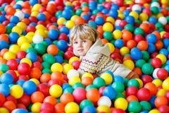 Criança que joga no campo de jogos plástico colorido das bolas fotografia de stock