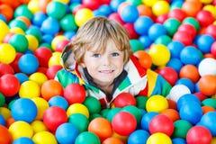 Criança que joga no campo de jogos plástico colorido das bolas fotos de stock