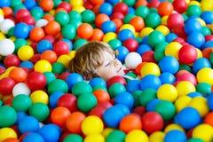 Criança que joga no campo de jogos plástico colorido das bolas fotos de stock royalty free