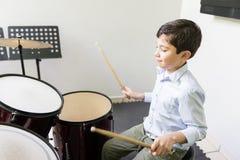 Criança que joga o cilindro na escola de música foto de stock