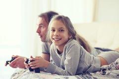 Criança que joga o jogo de vídeo com pai Fotografia de Stock Royalty Free