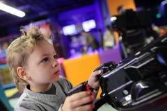 Criança que joga o jogo do tiro Foto de Stock