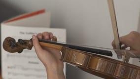 Criança que joga o violino com notas filme