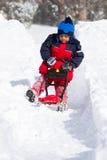 Criança que joga para limpar a neve com o brinquedo ao ar livre Foto de Stock Royalty Free
