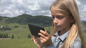 Criança que joga a tabuleta exterior no parque, uso Smartphone da criança na menina do prado na grama fotografia de stock royalty free