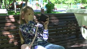 Criança que joga a tabuleta no campo de jogos no parque, menina que senta-se no banco, Smartphone 4K video estoque