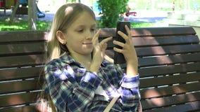 Criança que joga a tabuleta no campo de jogos no parque, menina que senta-se no banco, Smartphone 4K vídeos de arquivo