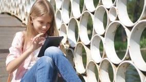 A criança que joga a tabuleta no parque, menina usa os Smartphones exteriores na natureza imagens de stock