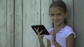Criança que joga a tabuleta pela menina da cerca que usa as crianças exteriores do smartphone que estudam 4K filme