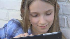 Criança que joga a tabuleta, criança Smartphone, mensagens da leitura da menina que consultam o Internet filme