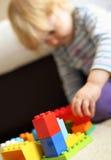 Criança que joga tijolos de Lego Imagens de Stock