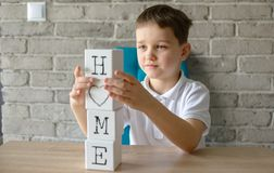 Criança que joga tijolos de madeira com as letras que fazem a casa da palavra Imagens de Stock