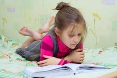 Criança que lê um livro Fotos de Stock