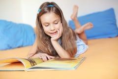 Criança que lê um livro Fotos de Stock Royalty Free