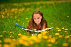 Criança que lê um livro ao encontrar-se Fotos de Stock