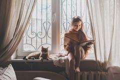 Criança que lê um livro com gato fotos de stock