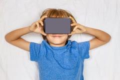 Criança que liying na cama branca com realidade 3D virtual, vidros do cartão de VR Fotografia de Stock Royalty Free