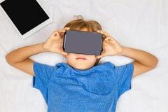 Criança que liying na cama com realidade 3D virtual, vidros do cartão de VR Fotografia de Stock Royalty Free