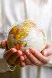 Criança que mantém um globo disponivel Fotografia de Stock Royalty Free
