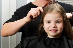 A criança que a menina faz o cabelo, corte de cabelo, ela sorri Foto de Stock