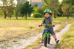 A criança que monta uma bicicleta Fotos de Stock