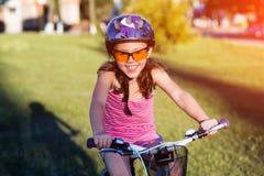 Criança que monta uma bicicleta A criança no capacete na bicicleta Fotografia de Stock
