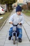 Criança que monta uma bicicleta do brinquedo Imagens de Stock Royalty Free
