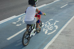 Criança que monta uma bicicleta na pista de bicicleta ou no trajeto do ciclo fora Imagem de Stock