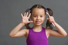Criança que mostra cinco ao guardar uma escova de dentes imagem de stock