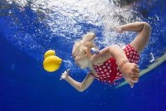Criança que nada debaixo d'água para o limão amarelo na associação azul fotografia de stock royalty free