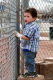 Criança que olha através da cerca Fotos de Stock Royalty Free