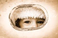 Criança que olha através do furo Fotografia de Stock Royalty Free